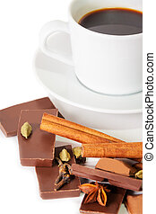 Cup of coffee, pieces of chocolate and spices isolated on white.