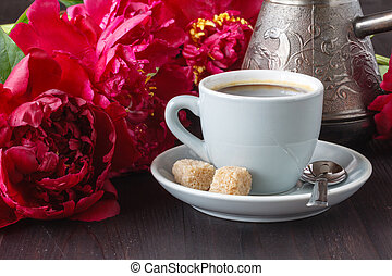 cup of coffee , pink peonies pattern on wooden background . Good morning