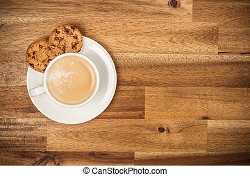 Cup of coffee served in porcelaine saucer on wooden table....