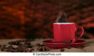 Cup of coffee standing on sackcloth, and cinnamon is slow steam. Slow motion