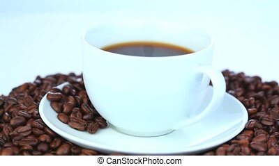 Cup of coffee surrounded by coffee