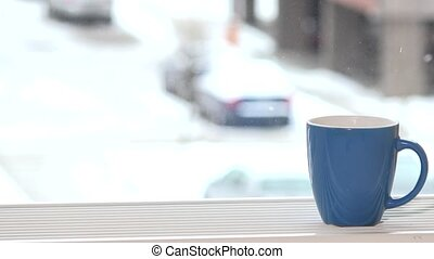 cup of coffee tea hot drink on window sill and snowflakes snow fall outdoor