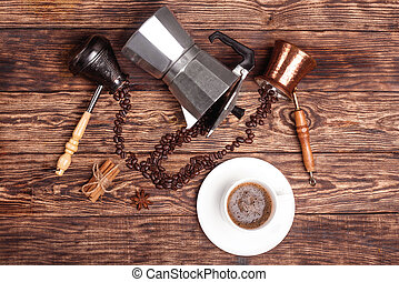 Cup of coffee, three coffeepots, cinnamon, anise, coffee beans on a wooden tray.  View from the top.