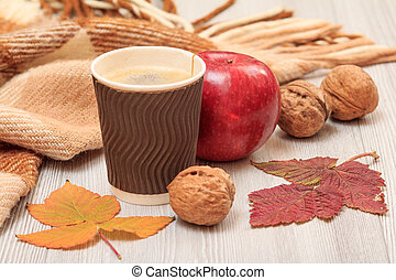 Walnut, cup of coffee, apple, checkered wool plaid and dry leaves on wooden boards. An autumn still llife.