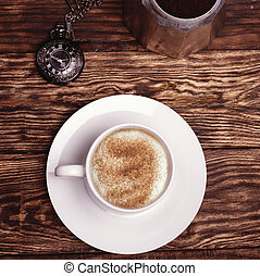 Cup of coffee, watch and coffeepot on a wooden background