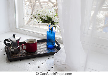 Cup of coffee with a blue vase on a wooden tray near the window