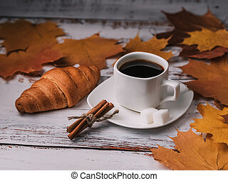 Cup of coffee with a croissant for a morning Breakfast in autumn