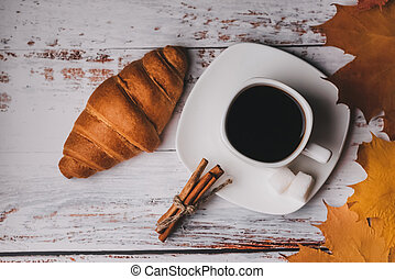 Cup of coffee with a croissant for a morning Breakfast in autumn on a white wooden table