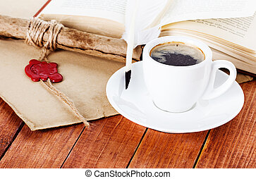 cup of coffee with a quill pen and parchment scroll of a book on wooden background
