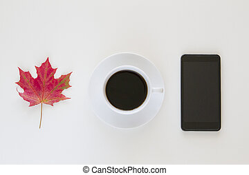 Cup of coffee with autumn leaf and cellphone on white background - Flat lay top view
