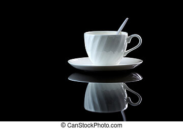 Cup of coffee with backlight on a black reflective background