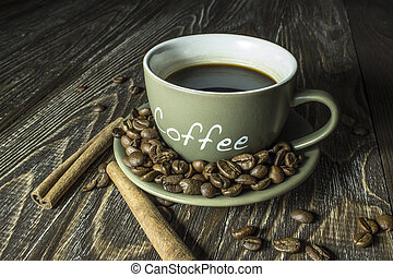 Cup of coffee with beans and cinnamon sticks on a wooden table