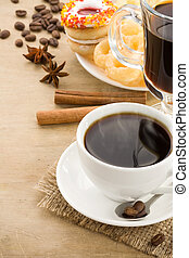 cup of coffee with beans and sweets