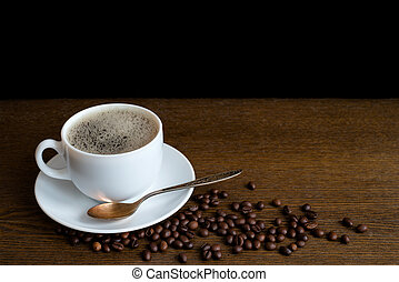 Cup of coffee with beans on a wooden table