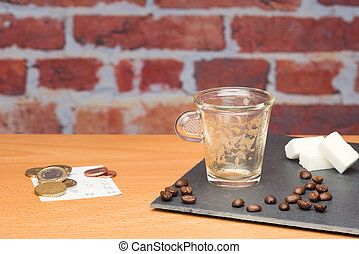 Cup of coffee with bill on brick wall