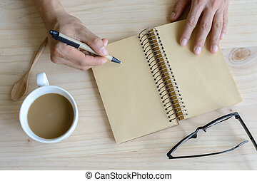 Cup of coffee with blank notebook on wooden desk