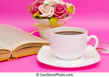 Cup of coffee with book isolated on pink background