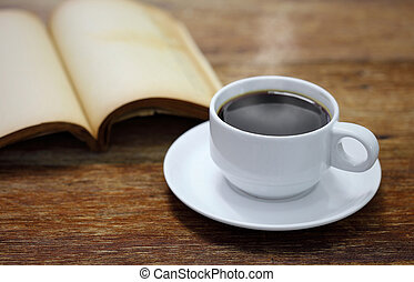 Cup of coffee with book on a wooden table