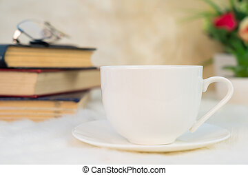 Cup of coffee with book stacked on table