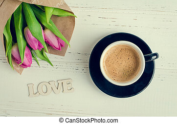 Cup of coffee with bouquet of pink tulips and wooden word LOVE