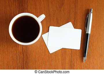 Cup of coffee with business cards and pen close-up