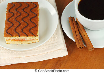 Cup of coffee with cherry cake on wooden background close-up