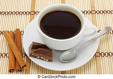 Cup of coffee with chocolate and cinnamon on wooden background