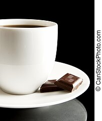 Cup of coffee with chocolate and saucer on black