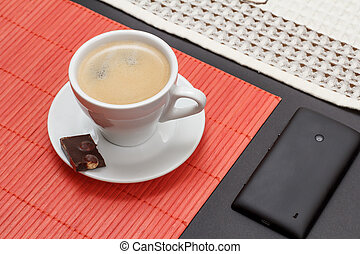 Cup of coffee with chocolate bar and mobile phone.