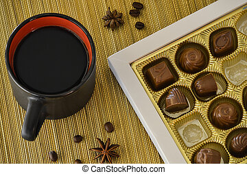 Cup of coffee with chocolate candies in a box