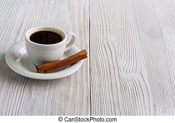 Cup of coffee with cinnamon stick on a white wooden background