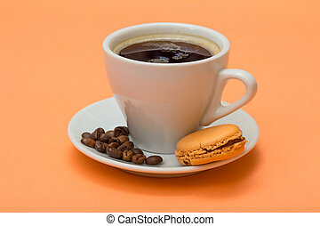 Cup of coffee with coffee beans and delicious macaron cake on peach background.