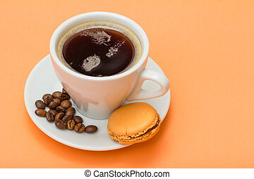 Cup of coffee with coffee beans and delicious macarons cake on peach background.