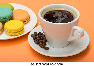 Cup of coffee with coffee beans and delicious macarons cakes