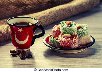 Cup of coffee with coffee beans and Turkish delight on saucer