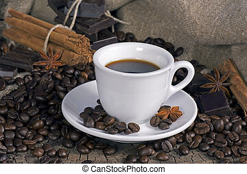 Cup of coffee with coffee beans, chocolate and spices