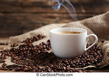 Cup of coffee with coffee beans on a brown wooden background