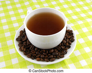Cup of coffee with coffee beans on a beautiful yellow background