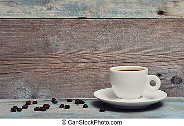 Cup of coffee with coffee beans on vintage wooden background