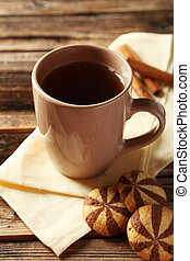 Cup of coffee with cookies on brown wooden background