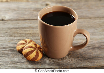 Cup of coffee with cookies on grey wooden background