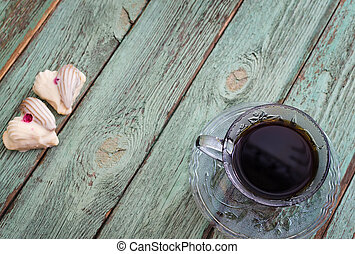 Cup of coffee with cookies on old turquoise wooden board.
