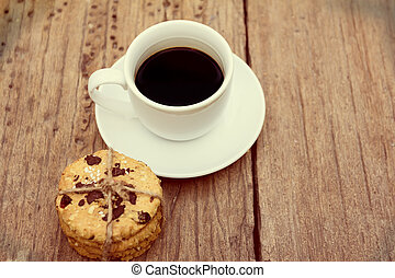 cup of coffee with cookies on wooden table
