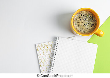 Cup of coffee with copybooks on color background, top view