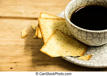 Cup of coffee with crackers on wood table.