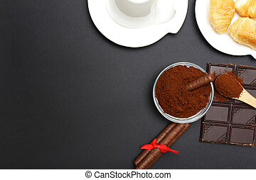 cup of coffee with croissant and chocolate on background