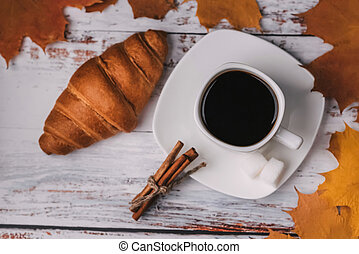 Cup of coffee with croissant and cinnamon sticks on a wooden table with autumn orange maple leaves