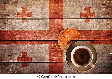 Cup of coffee with croissant and flag