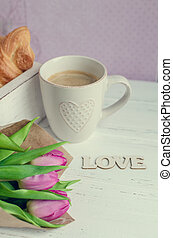 Cup of coffee with croissants, bouquet of pink tulips and wooden word LOVE