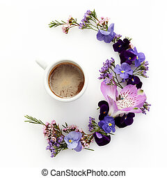 Cup of coffee with flowers round frame. Flat lay, top view